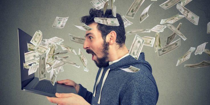 Pieniądze wylatujące z laptopa zdziwiony człowiek