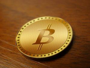 BTC moneta elektroniczna wygląd złoty okrągły pieniądz biurko