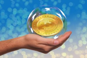 bitcoin moneta bańka mydlana otwarta dłoń błękitne tło