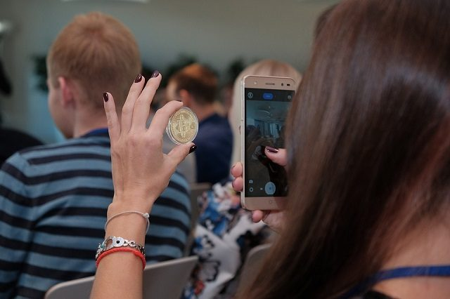 kobieta robi zdjęcie trzymanemu bitcoin tło stanowią inne osoby sala wykładowa