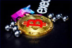 bitcoin na czarnym blacie obok metalowych kulek