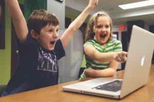 Dzieci przy komputerze sukces radość zwycięstwo