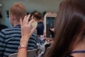 Kobieta robiąca smartfonem zdjęcie monecie Bitcoin