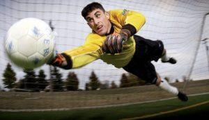 Piłka nożna bramkarz w żółtej koszulce łapie piłkę broni bramki