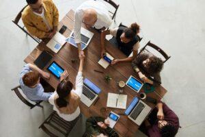 Grupa ludzi pracuje wspólnie na laptopach