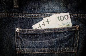 Banknoty o nominale 100 zł w tylnej kieszeni spodni